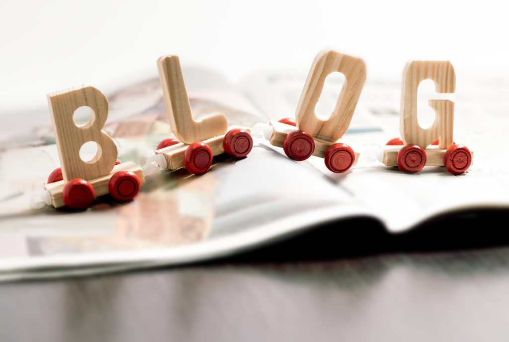 Word - Blog - in wooden letters on small red wheels spanning the pages of an open magazine in a communication and social media concept